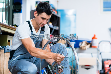 mann als fahrradmechaniker in der werkstatt