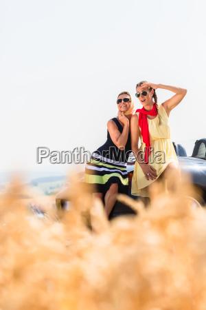 women having joyride in convertible car
