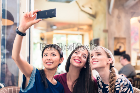 three young women making selfie photos