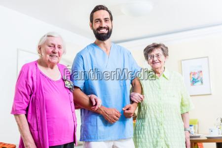 caregiver with senior women in nursing