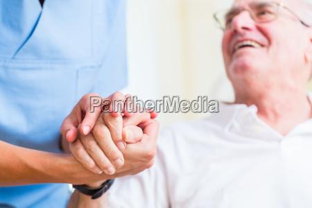 krankenschwester holding hand von aelteren mann