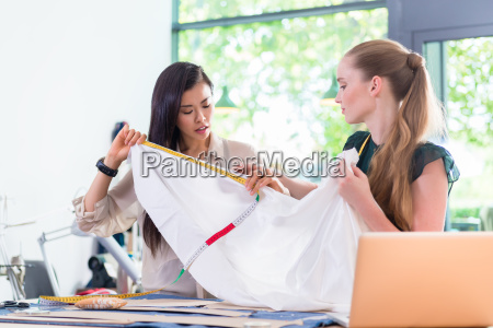 young fashion designer women measuring cloth
