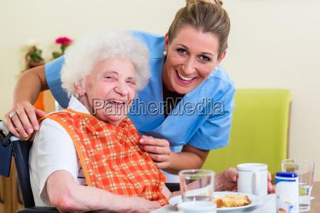 krankenschwester, mit, älterer, frau, die, mit, mahlzeit - 21499195