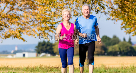 senior woman and man running doing