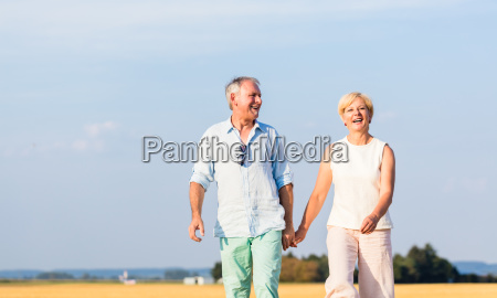senior woman and man holding hands
