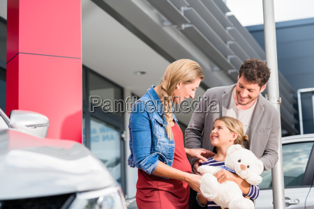mother father and child buying car