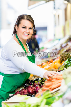 saleswoman with fruit and vegetables at
