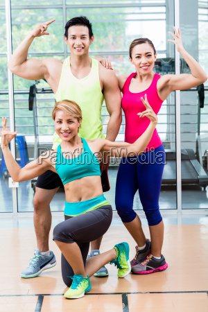 muscular man amongst two sportive women
