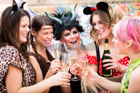 girls at carnival parade clinking glasses