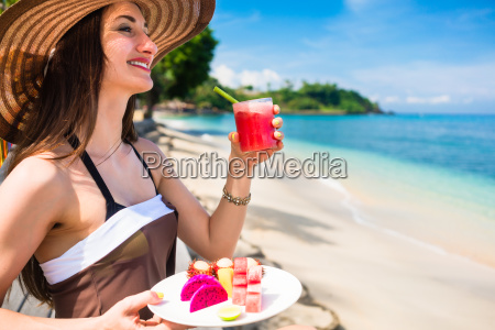 woman at tropical beach eating fruit