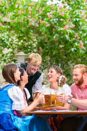 friends clinking glasses in beer garden