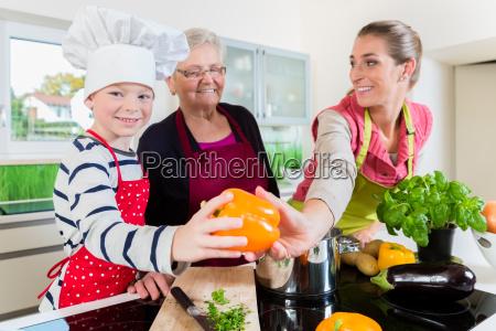 oma mama und sohn beim kochen