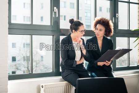 two young colleagues reviewing business reports