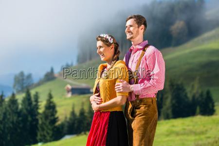 couple in tracht on alp mountain