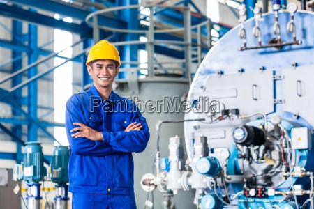 stolzer asiatischer arbeiter in der produktionsfabrik