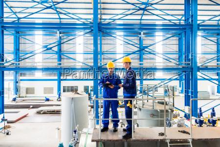 workers in large metal workshop checking