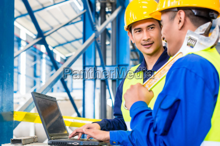worker in production plant with laptop