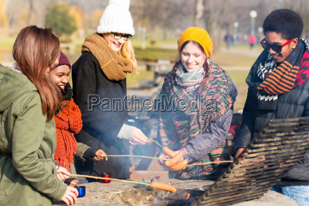 group of young people roasting sausages