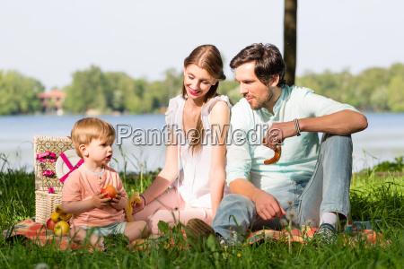 familie mit picknick am see auf