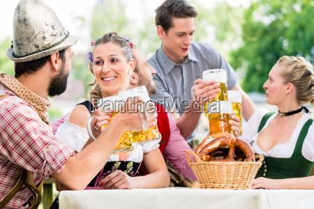 friends in bavarian beer garden drinking