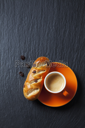 chocolate bun with raisins and cup