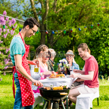 man grilling meat on garden barbecue