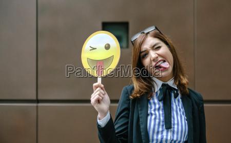 geschaeftsfrau die emoji laechelt mit der