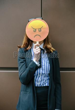versteckendes gesicht der frau hinter emoji
