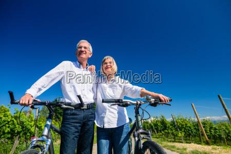 senior couple enjoying view on bike