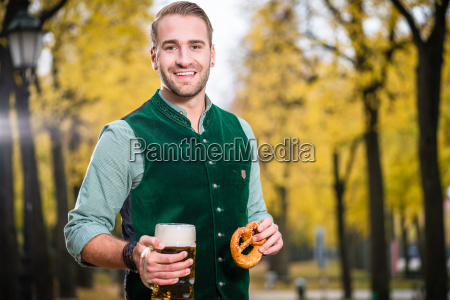 man in traditional bavarian tracht drinking