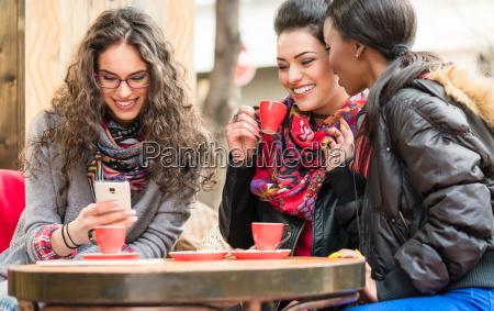 frauen im cafe zeigt bilder auf