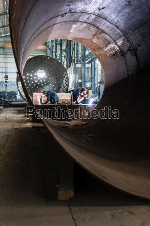 two workers welding in a factory