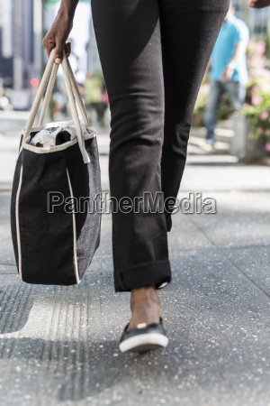 woman with shopping bag partial view