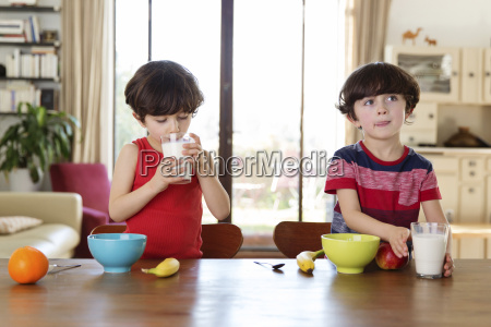 zwillingsbrueder am fruehstueckstisch trinken milch