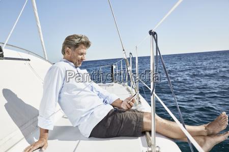 mature man sitting on his sailing