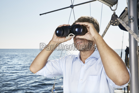 mature man using binoculars on his