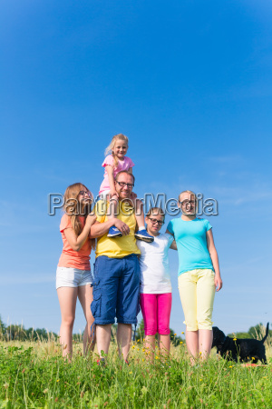 family standing on meadow father