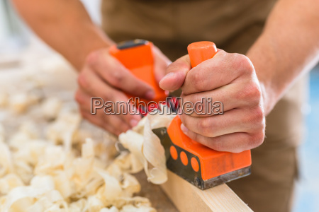 carpenter with wood planer working on