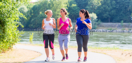 grupa kobiet biegnacych nad jeziorem joggingu