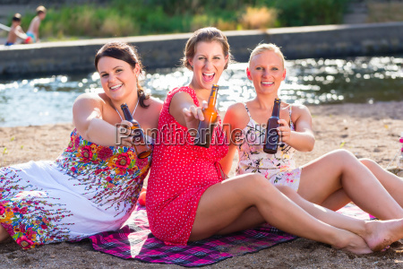 friends drinking beer at river beach