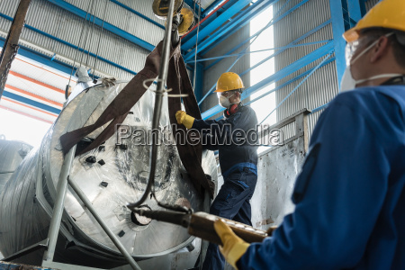 workers handling equipment for lifting industrial