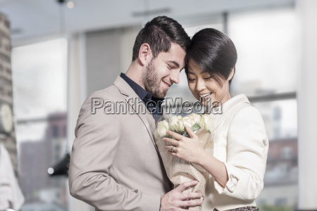 man handing over roses to woman