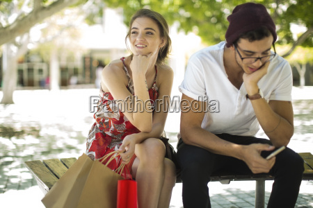 young couple sitting on bench with