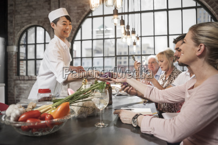 female chef handing over beetroot to