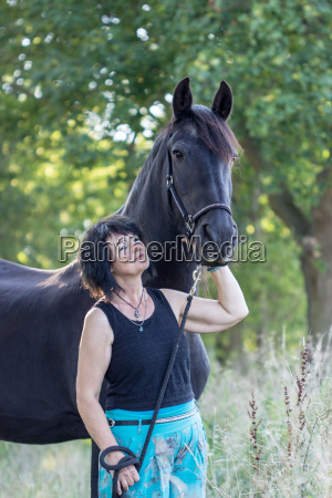 brunette woman with black horse in