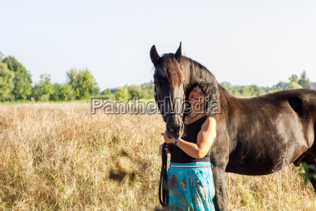 brunette woman with black horse on
