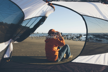 man framed by camping tent sitting
