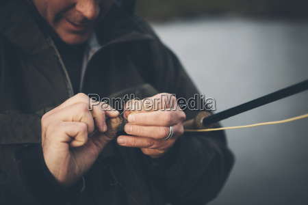 middle aged man fly fishing on