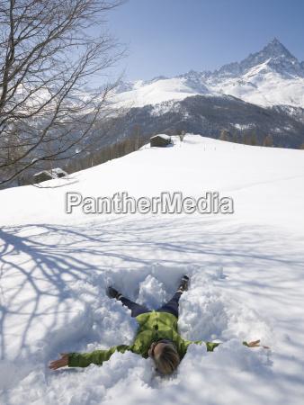 frau macht schnee engel in bergwiese