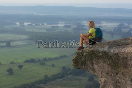 woman sitting on sandstone overhang watching